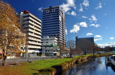Christchurch, New Zealand - May 27, 2012: The second tallest building in the city, The Price Waterhouse building, on the banks of the Avon River awaits demolition in the autumn sunshine.