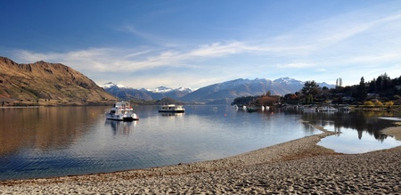 Lake Wanaka and boats with the Southern Alps in the background  Central Otago, New Zealand  In the foreground note how low the lake level is after one of the hotest and driest summers on record  photo