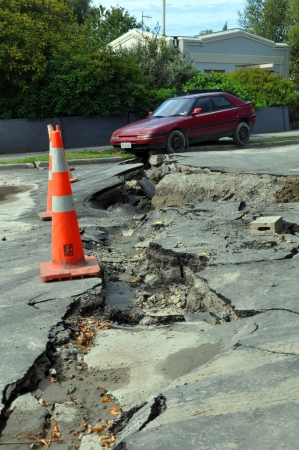 Christchurch, New Zealand - February 24, 2011: Car falls into a crack caused by the largest and most devastating earthquake Christchurch has experienced. Stock Photo - 14147722