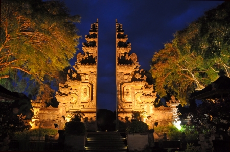 Welcome to Bali - the gates to paradise carved in stone and flanked by two enormous Banyon trees. Night scene. Stock Photo