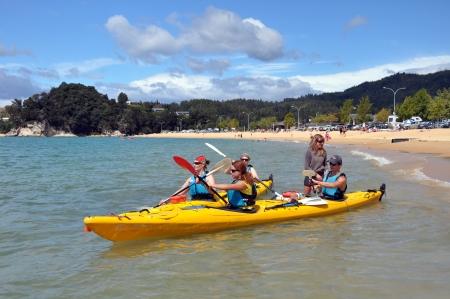 new zealand beach: Kaiteriteri, New Zealand - January 22, 2012: Young people take off on their Kayaks from Kaiteriteri Beach in the famous Abel Tasman National Park.