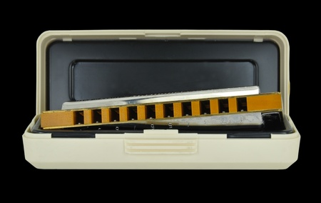 harmonica: A wooden blues harp or mouth organ and case isolated on a black background. The Blues harp is used in Blues music and sometimes in Jazz and Country music.