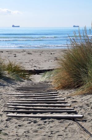 Brighton beach on a perfect summer day with wooden steps. Christchurch, New Zealand. In the background ships await their turn to unload cargo at the Port of Lyttleton.