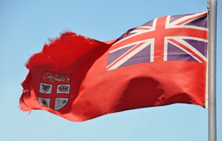 fijian: Red Fijian Flag Fluttering in The Breeze  This Merchant Ensign design includes a Union Jack and Shield of arms on a red background  Stock Photo