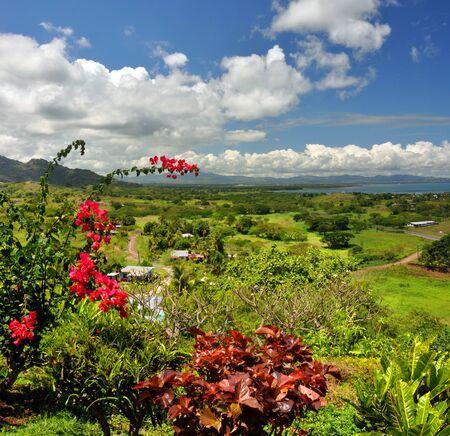 Vertical panorama of the Fijian west coast  In the foreground Hibiscus - the Fijian national symbolic flower  In the background Nadi and Denarau Island  Stock Photo