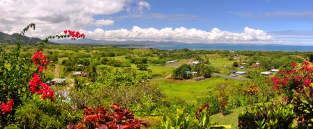 Panorama of the Fijian west coast. In the foreground Hibiscus - the Fijian national symbolic flower. In the background Nadi and Denarau Island. Stock Photo
