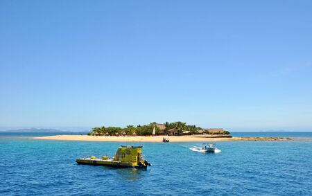South Sea Island, Fiji - October 01, 2012: A boat comes to ferry tourists to the island for a day of snorkeling, entertainment and underwater viewing of the reef via the submarine in the foreground.