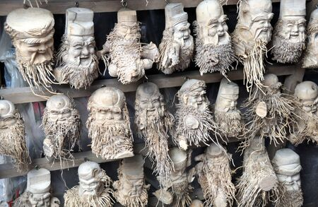 Bamboo root carved figures of happy old men at a stall in Hoi An market, Vietnam