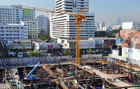 dozens: Bangkok, Thailand - November 27, 2011: A busy commercial building construction site with dozens of workers and seven cranes in downtown Bangkok, Thailand.