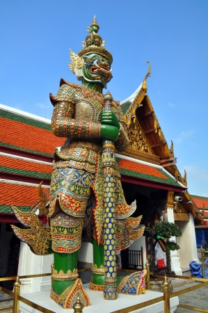 grand palace: Giant and ferocious looking mosaic statue guards the entrances to the Grand Palace  situated on the banks of the Chao Phraya River in the Phra Nakhon District of Bankok Thailand.
