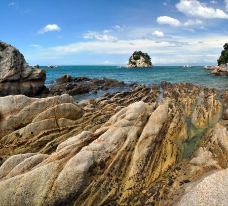 tasman: Kaiteriteri rocks vertical panorama, Abel Tasman National Park, New Zealand  In the background are the towns of Mapua, Motueka and Nelson