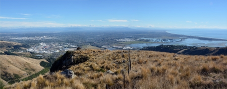 Aerial Panoramic view of Christchurch City and the Canterbury Plains from the top of the Port Hills. To the left is the city and to the right the Estuary and Pacific Ocean. In the distance are the Southern Alps.  Stock Photo