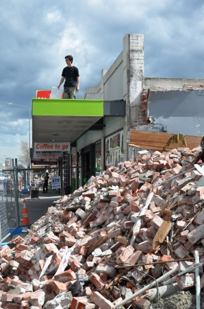 29 September 2010 - Christchurch, New Zealand - September 29, 2010: A young  businessman views the devastation of a shop in Riccarton Road - one of the hardest hit areas in the earthquake on September 29, 2010 in Christchurch. Stock Photo - 18777643