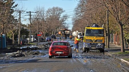 Christchurch, New Zealand - June 15, 2011:  Construction workers remove tons of liquefaction which cover Retreat Road in Avonside after recent earthquakes and after-shocks on June 15, 2011 in Christchurch.