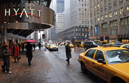 42nd: New York, USA - April 08, 2014  Waiting for a taxi outside the Grand Hyatt hotel on East 42nd Street on a wet morning