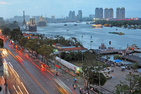Ho Chi Minh City, Vietnam - June 07, 2011  The Saigon River in the early evening  In the foreground the motorcycles and cars rush home along Ton Duc Thang street on a wet evening