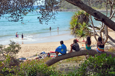 Noosa, Australia - July 05, 2009: Children sitting on a tree branch watching the swimers at a surfing beach in the Noosa National Park, Queensland Australia.