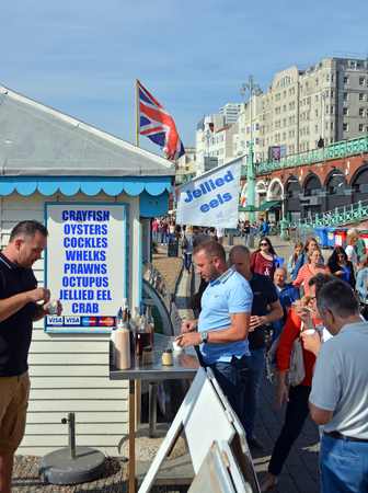 fish shop: Brighton, United Kingdom - September 28, 2014: Tourists eat Jellied Eel on the beach on a Summer day at Brighton on the south coast of England.