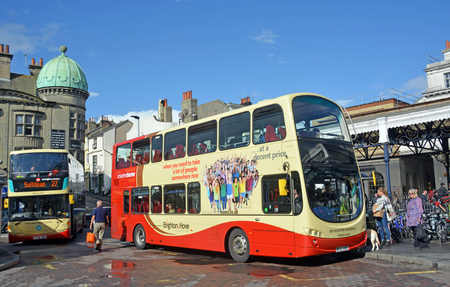 decker: Brighton, United Kingdon - October 10, 2014: Tourists taking a double decker bus from outside  Brighton Railway Station.