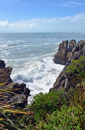 new zealand flax: Massive waves crashing on the rocks at Punakaiki, Looking north up the West Coast towards Karamea, New Zealand Stock Photo