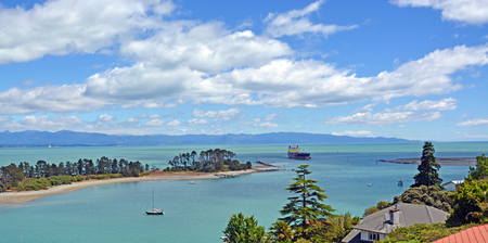 nelson: A container ship sails through the famous Cut - between Haulashore Island and The Boulder Bank in Nelson, New Zealand