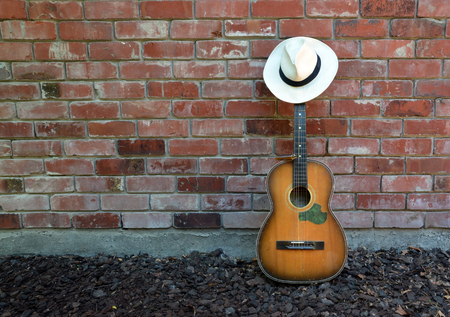 Guitar player takes a break leaving old acoustic guitar, Blues Harp and Panama Hat leaning against a brick wall. Stock Photo