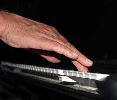 ivories: Tickling The Ivories - closeup of a hand playing the piano at night under a spotlight.