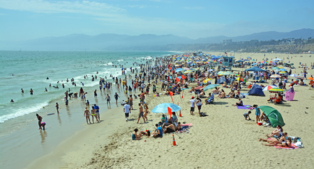 flocking: Los Angeles, USA - July 14, 2013: Panoramic view of thousands of locals and tourists flocking  to Santa Monica beach on a hot Summer day. Editorial