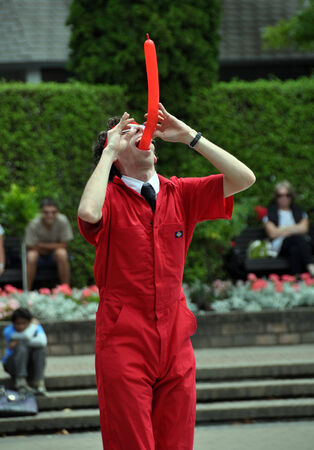 contortion: Christchurch, New Zealand - January 29, 2011: Combining comedy, contortion and stunts, Jonathan Burns from the USA swallowing a balloon at the 18th World Buskers Festival.