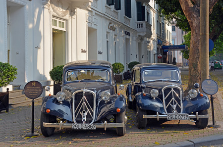 traction: Hanoi Vietnam  April 15 2015: Two Citroen Traction 15 Familiale 1956 sightseeing cars outside the Sofitel Metropole Hotel. Editorial