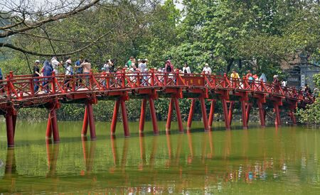adult vietnam: Hanoi Vietnam  April 14 2015: Tourists on the Red Bridge also known as The Huc Bridge over Lake Hoan Kiem in central Hanoi on a Spring day.