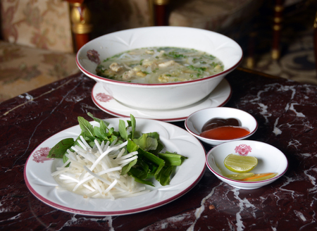 ga: Ho Chi Minh City, Vietnam - April 05, 2015: Chicken Noodle Soup (Pho Ga) is the national dish in Vietnam. It is served here at the Majestic Hotel  with Chilli sauce, Limes, Chillies, Bean Sprouts and Lemon Grass which may optionally be added to the soup.