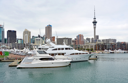motor launch: Aukland, New Zealand - August 04, 2015: Luxury Cruising Boats in the Viaduct Basin boat harbour. Auckland city and Skytower in the background.