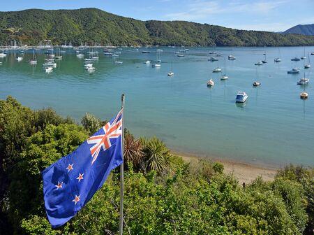 bandera de nueva zelanda: Bandera de Nueva Zelanda con orgullo que agita en un día soleado de primavera en Marlborough Sounds.