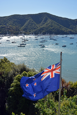 fluttering: New Zealand Flag Proudly Fluttering on a Spring Day in Marlborough Sounds.