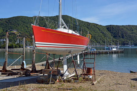 chandler: Red Yacht being repaired at a Shipyard in Waikawa Marina, Picton, New Zealand. Stock Photo