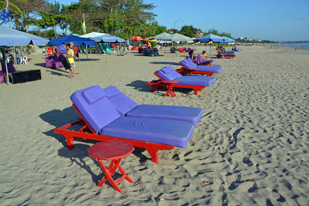 Bali, Indonesia - September 13, 2015: Chairs  Umbrellas awaiting tourists on Legian Beach.