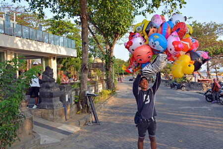 Bali, Indonesia - September 16, 2015: Young male vendor of Animal shaped childrens Balloons at Legian Beach. Editorial
