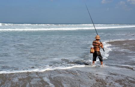 legian: Bali, Indonesia - September 14, 2015: Balinese Fisherman Surf Casting on a summer day at  Legian Beach.