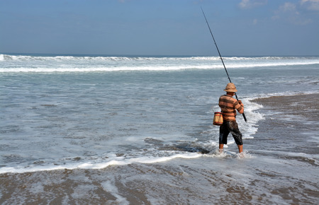 Bali, Indonesia - September 14, 2015: Balinese Fisherman Surf Casting on a summer day at  Legian Beach.