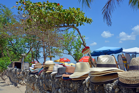 legian: Bali, Indonesia - September 14, 2015: Entrance to Legian Beach including bar, trees and sun Umbrellas and Hats for sale or rent. Editorial