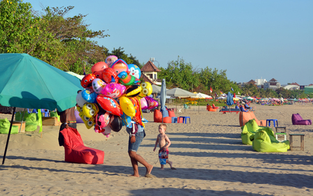 Bali, Indonesia - September 13, 2015: Vendor of Animal Shaped Balloons being chased by a small boy at Legian Beach. Editorial