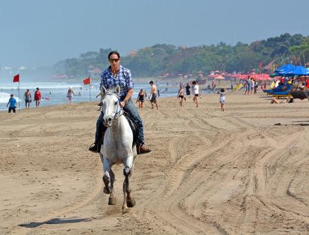legian: Bali, Indonesia - September 15, 2015: Young Woman Riding a Horse on Legian Beach on a Summer morning. Editorial