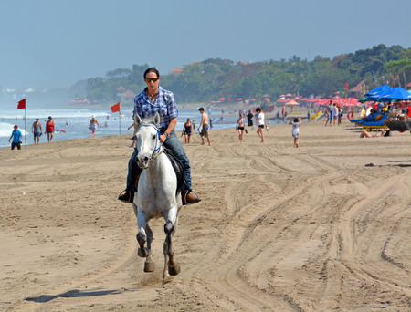 Bali, Indonesia - September 15, 2015: Young Woman Riding a Horse on Legian Beach on a Summer morning. Editorial