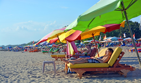 legian: Bali, Indonesia - September13, 2015: Tourists Snooze on colourful recliner chairs at Legian Beach in the afternoon.
