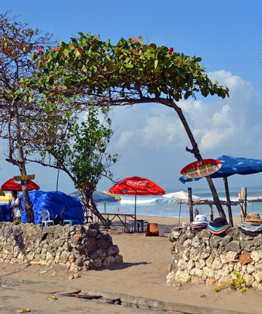 Bali, Indonesia - September 14, 2015: Entrance to Legian Beach including bar, trees and sun Umbrellas and Hats for sale or rent. Editorial