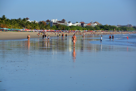 legian: Bali, Indonesia - September 13, 2015: Late Afternoon at Low Tide tourists strolling on Legian Beach. Editorial