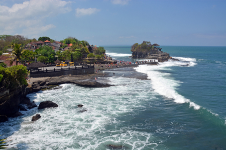 legian: Bali, Indonesia - September 17, 2015: Tanah Lot Hindu Temple on a Rock isolated by the high Tide with tourists in the foreground. Editorial