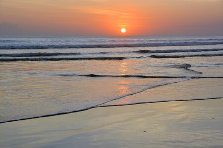 Sunset and wave patterns at Low Tide on Legian Beach, Bali, Indonesia
