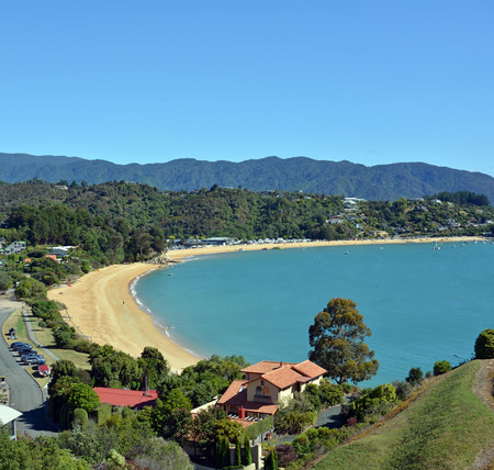 tasman: Little Kaiteriteri vertical panorama featuring in the foreground the golden sands of Little Kaiteriteri beach and luxury houses. In the background is the main Kaiteriteri beach and camping ground and the Able Tasman National Park. Stock Photo